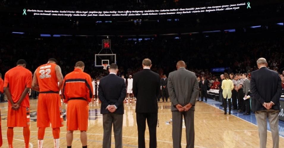 22.dez.2012 - Integrantes do time de basquete Syracuse Orange fazem um minuto de silêncio pelas vítimas do massacre na escola Sandy Hook, em Connecticut, enquanto os nomes das 26 pessoas mortas no tiroteio percorrem um letreiro luminoso ao fundo da quadra do Madison Square Garden, em Nova York