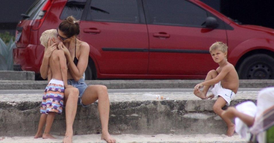 23.dez.2012 - Fernanda Lima curte o domingo na praia do Leblon, no Rio de Janeiro, com os dois filhos