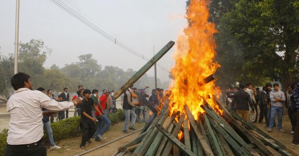 23.dez.2012 - Manifestantes indianos queimam postes de madeira que foram derrubados de barricadas durante um protesto pedindo mais segurança para as mulheres após o estupro de uma estudante na semana passada, em Nova Déli, na Índia