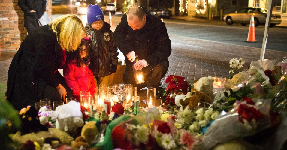 23.dez.2012 - O casal Norma Macchia e Steven Macchia, acompanhado dos filhos, depositam flores e acendem velas em memorial às vítimas do massacre na escola Sandy Hook, em Newtown, Connecticut, ocorrido no último dia 14