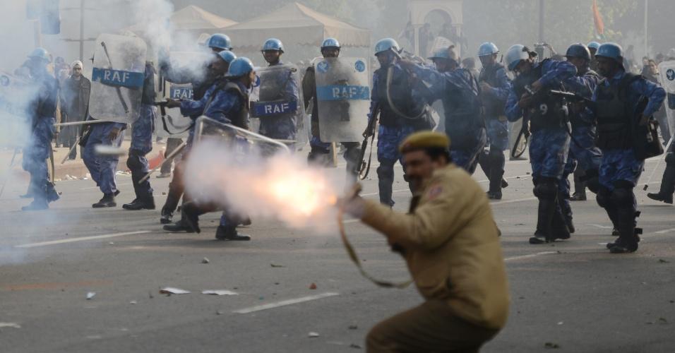 23.dez.2012 - Policial indiano atira bomba de gás lacrimogêneo contra manifestantes, neste domingo (23), durante um protesto pedindo mais segurança para as mulheres após o estupro de uma estudante na semana passada. Os manifestantes exigem justiça e a criação de leis mais rigorosas contra crimes sexuais