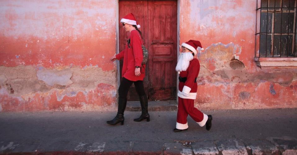 24.dez.2012 - Alexander, vestido de Papai Noel, caminha ao lado da mãe em Antigua (a 42 km da Cidade da Guatemala)