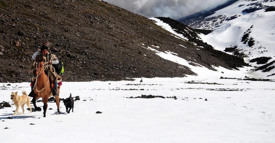 24.dez.2012 - Chileno cavalga próximo ao vulcão Copahue, que entrou em atividade e está expelindo cinzas, na região de Biobio (a 650 km de Santiago), zona limítrofe entre o Chile com a Argentina