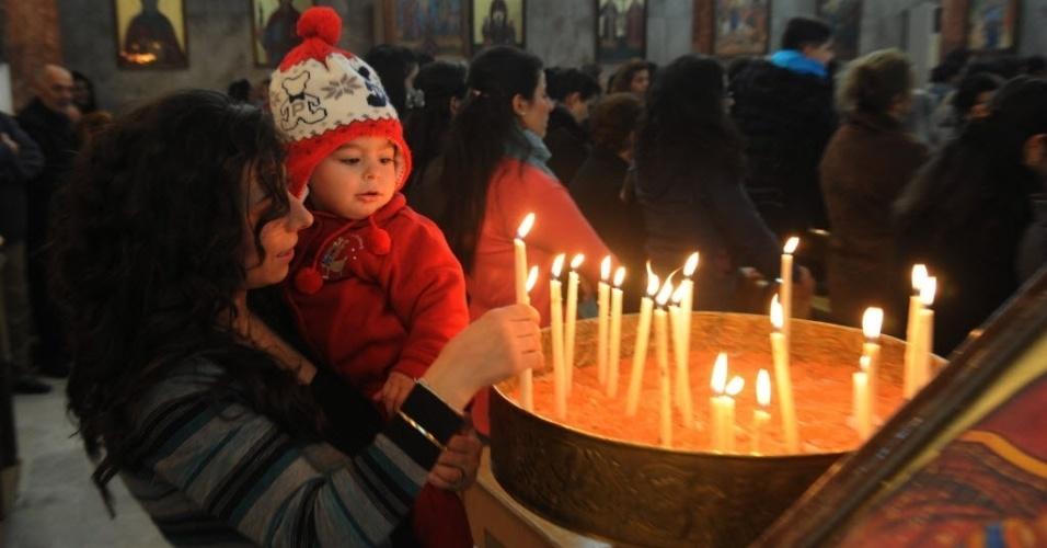 24.dez.2012 - Mulher síria acende vela em igreja ortodoxa cristã cristã em Bab Tuma, região predominantemente cristã em damasco, capital da Síria, nesta segunda-feira (24), véspera do Natal