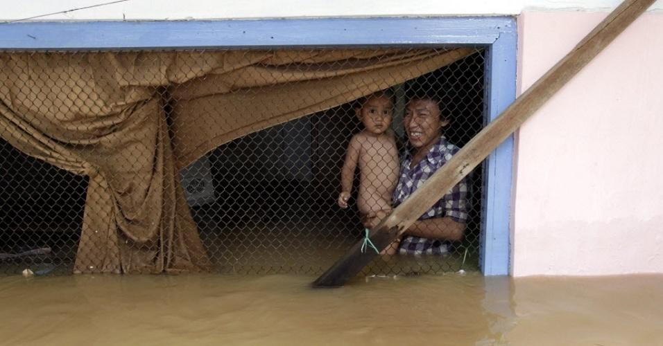 24.dez.2012 - Pai e filho observam estragos causados pela chuva em Jacarta, na Indonésia