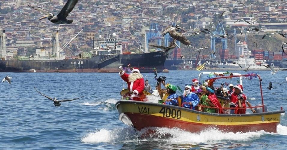 24.dez.2012 - Pescadores vestidos de Papai Noel passam de barco pela costa de Valparaíso, no Chile, nesta segunda-feira (24), véspera do Natal. Todos os anos, pescadores de Valparaíso organizam essa viagem para a entrega de presentes na praia