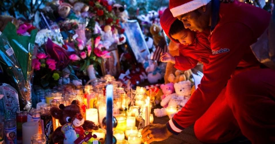 24.dez.2012 - Vestidos de Papai Noel, pai e filho acendem vela em memorial para as vítimas do atirador da escola primária de Sandy Hook, em Newtown, Connecticut (EUA), que matou 27 pessoas, incluindo 20 crianças, e depois se matou, no último dia 14. Cartas e objetos para homenagear as vítimas chegam de todas as partes do país