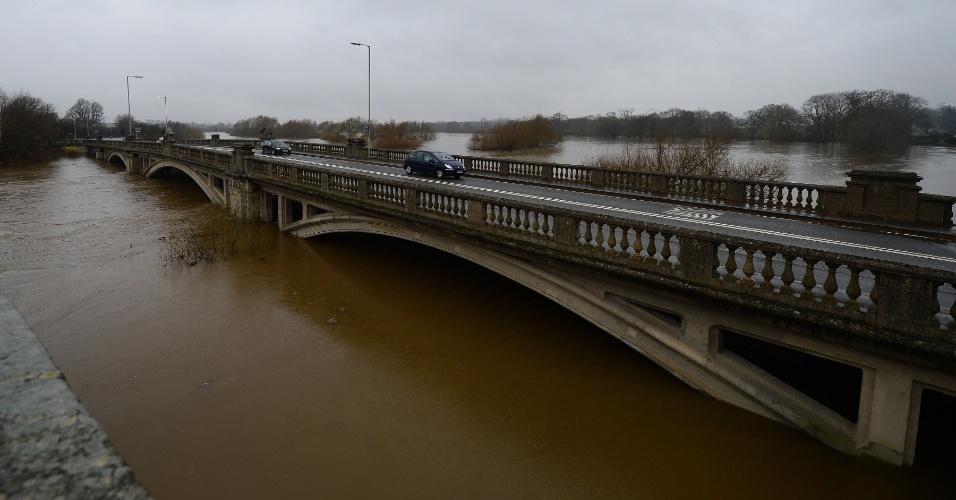 24.dez.2012 - No vilarejo inglês de Atcham, perto da cidade de Shrewsbury, carros trafegam em ponte sobre o rio Severn, cujo nível da água subiu bastante após as fortes chuvas dos últimos dias