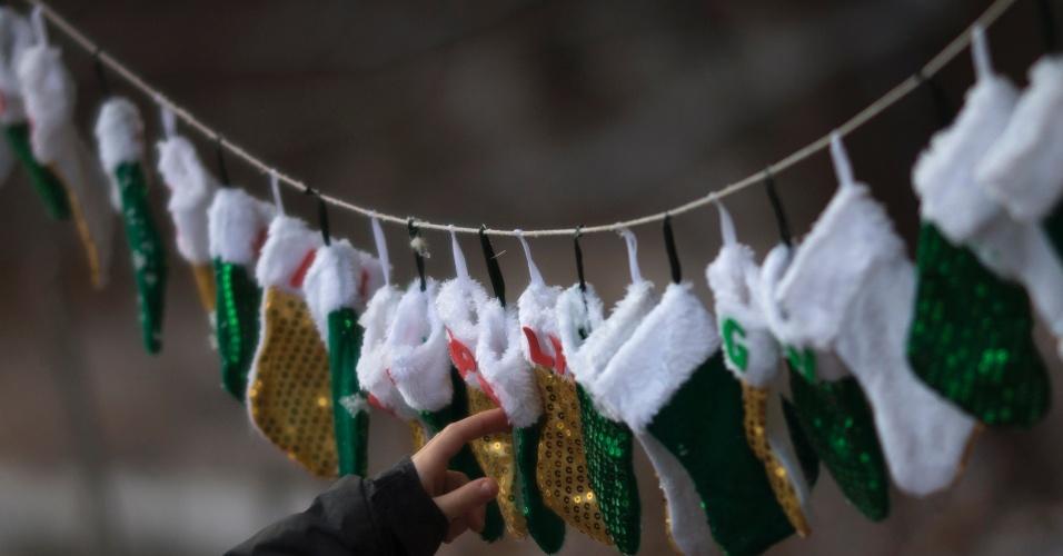 25.dez.2012 - Menino toca em meias -- que representam os mortos no tiroteio da escola primária de Sandy Hook -- expostas em um memorial construído em Newtown, em Connecticut (EUA), mesmo local da tragédia