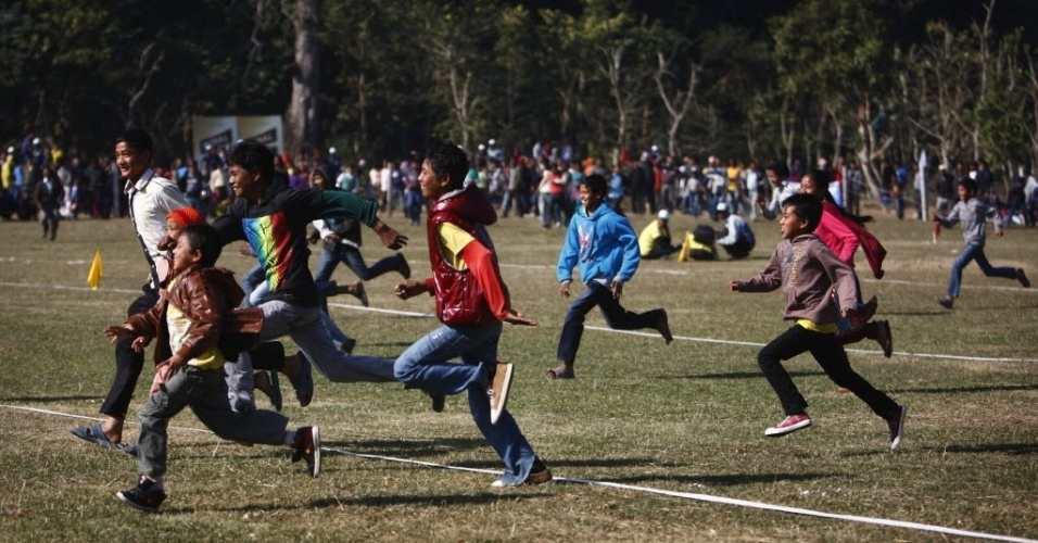 Crianças correm para assistir ao jogo de futebol entre elefantes no Nepal; o evento teve ótimo público
