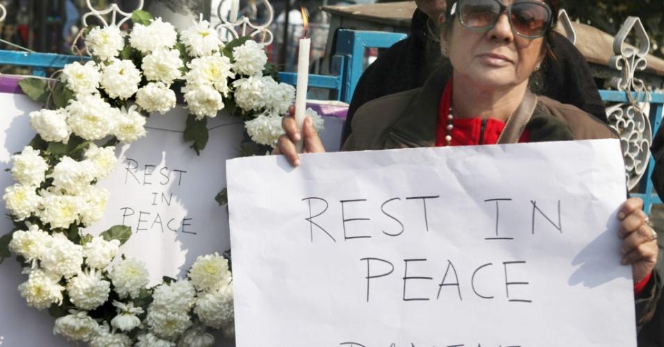 """29.dez.2012 - Mulher acende vela e exibe um cartaz onde se lê """"descanse em paz"""" durante um ato em Calcutá, na Índia, em memória da estudante que foi vítima de um estupro coletivo em Nova Déli, na noite do dia 16 de dezembro. A universitária de 23 anos morreu na noite desta sexta-feira (28) em um hospital de Cingapura, onde estava internada. Seis homens estupraram a jovem quando ela seguia viagem em um ônibus. Ela foi jogada pelos agressores do ônibus em movimento"""