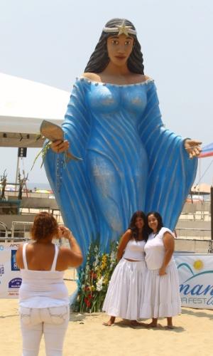 29.dez.2012 - Turistas registram fotos ao lado de imagem gigante de Iemanjá na praia de Copacabana, no Rio de Janeiro