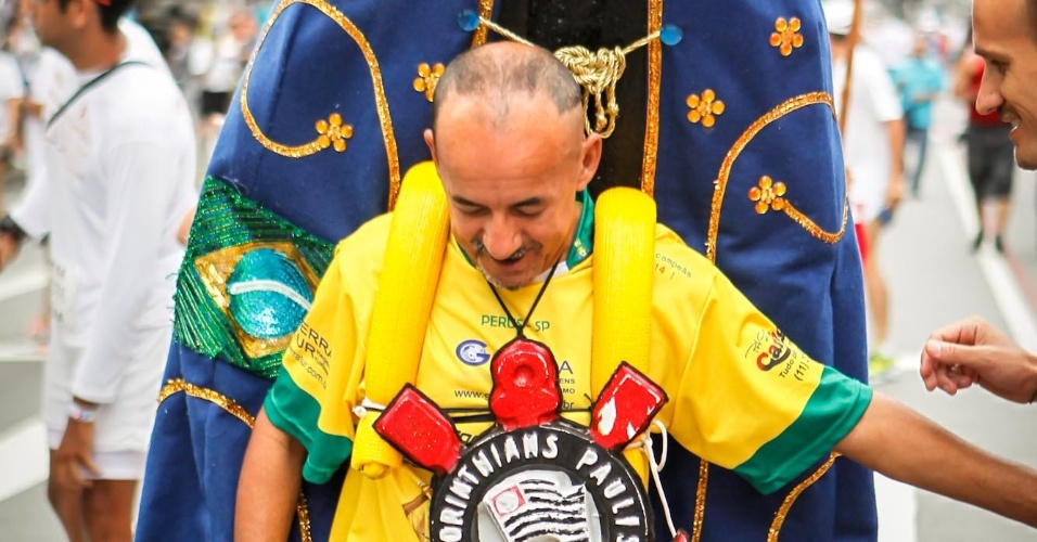 Carregando imagem de Nossa Senhora, com símbolo do Corinthians no pescoço e fazendo embaixadinhas, participante da São Silvestre leva animação à prova