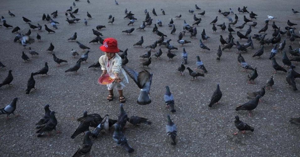 1º.jan.2012 - Criança alimenta pombos no cais de Yangon (Mianmar)