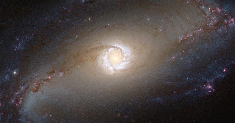 1.jan.2013 - O telescópio Hubble capturou o anel de uma estrela em formação no coração da galáxia NGC 1097, que fica na Constelação da Fornalha, a 45 milhões de anos-luz de distância da Terra - o anel do corpo celeste tem cerca de 5.000 anos-luz de diâmetro. Também no centro desta galáxia espiral, há um buraco negro supermassivo (com 100 milhões de vezes a massa do Sol) que está sugando matéria ao seu redor, o que faz a região brilhar intensamente devido à radiação e à emissão de nuvens de hidrogênio ionizado