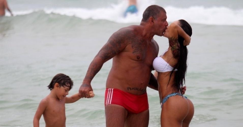 2.jan.2013 De sunga vermelha, Alexandre Frota beija a mulher Fabiana na praia da Barra da Tijuca