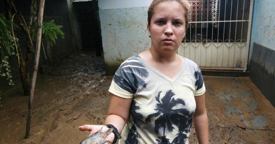 03.jan.2012 - Após a enchente, Marcela Gomes Coelho, 32, encontrou um peixe em sua casa no distrito de Xerém, em Duque de Caxias (SP)