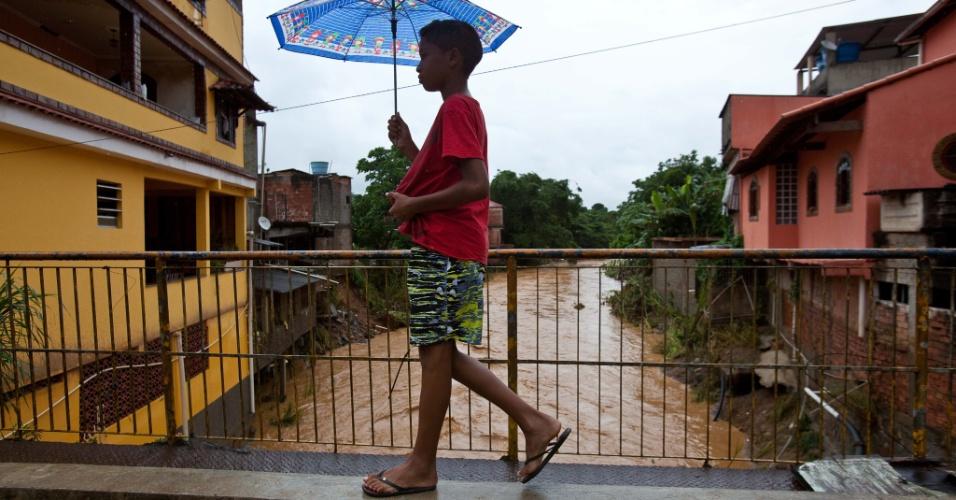 3.jan.2013 - Menino caminha em ponte sobre rio que transbordou em enchente ocorrida após forte chuvas na madrugada desta quinta-feira (3), em Xerém, Duque de Caxias. Um homem morreu, após o desabamento de uma casa. Cerca de 182 pessoas foram desalojadas, segundo a Defesa Civil