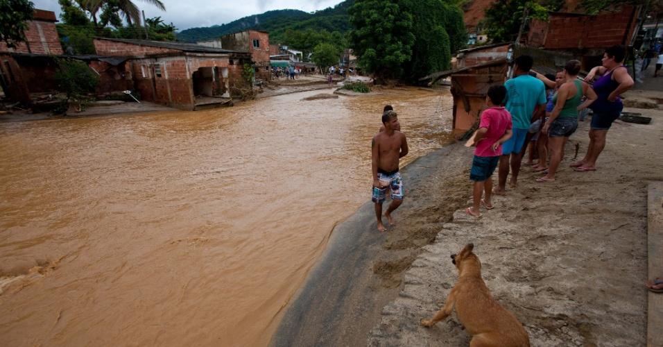 3.jan.2013 - Moradores observam correnteza em rua tomada pela enchente após fortes chuvas em Xerém, Duque de caxias, nesta quinta-feira (3)