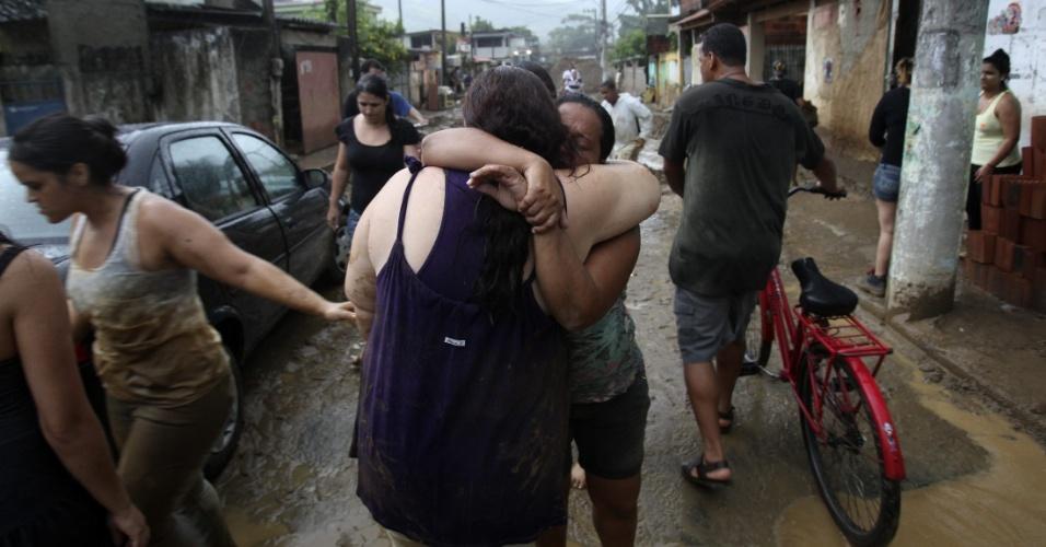 3.jan.2013 - Mulheres se abraçam após enchente ocorrida em Xerém, Duque de Caxias, após forte chuva na madrugada desta quinta-feira (3). A tragédia deixou um morto e desalojaram 182 pessoas, segundo balanço parcial divulgado pela Defesa Civil estadual