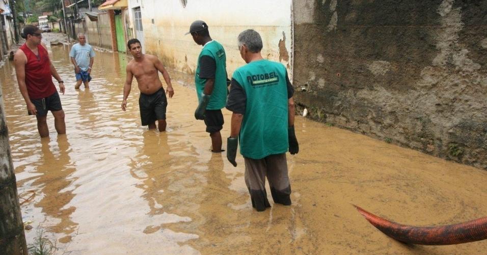 3.jan.2013 - Moradores tentam drenar lama de rua no bairro de Xerém, em Duque de Caxias (RJ), que ficrou alagado após forte chuva que caiu durante a madrugada. Um homem morreu, após o desabamento de uma casa. Cerca de cem pessoas foram desalojadas, segundo a Defesa Civil