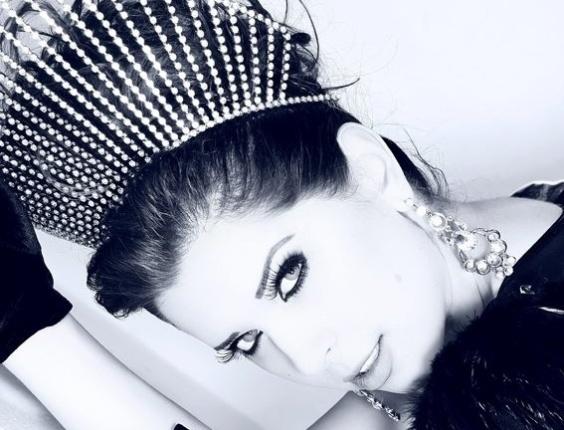 Andressa posa com roupa de luxo e coroa