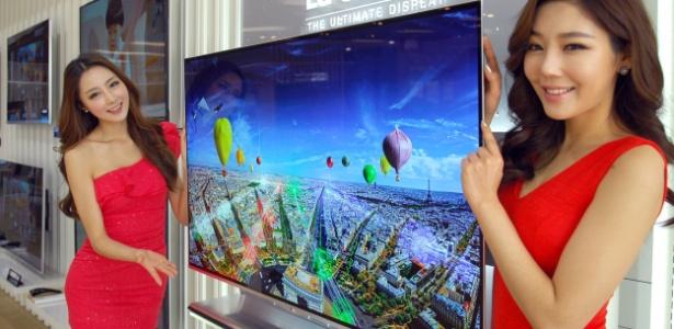 Expositoras posam ao lado de televisor de 55 polegadas da LG com resolução 4k e tela de 55 polegadas - AFP