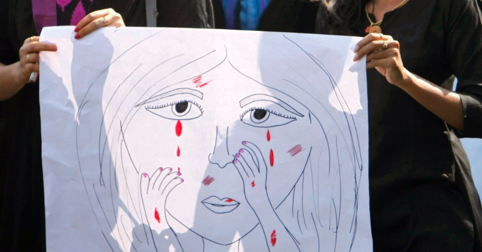 4.jan.2013 - Estudantes indianas seguram cartaz com desenho de mulher chorando, enquanto participam de uma marcha, em Hyderabad, India, nesta sexta-feira (4),  em memória à jovem vítima de estupro coletivo. Cinco homens são acusados de estuprar, por horas, uma estudante de 23 anos, em um ônibus em movimento, em Nova Déli, na Índia. A vítima morreu no dia 28 de dezembro, por conta dos ferimentos