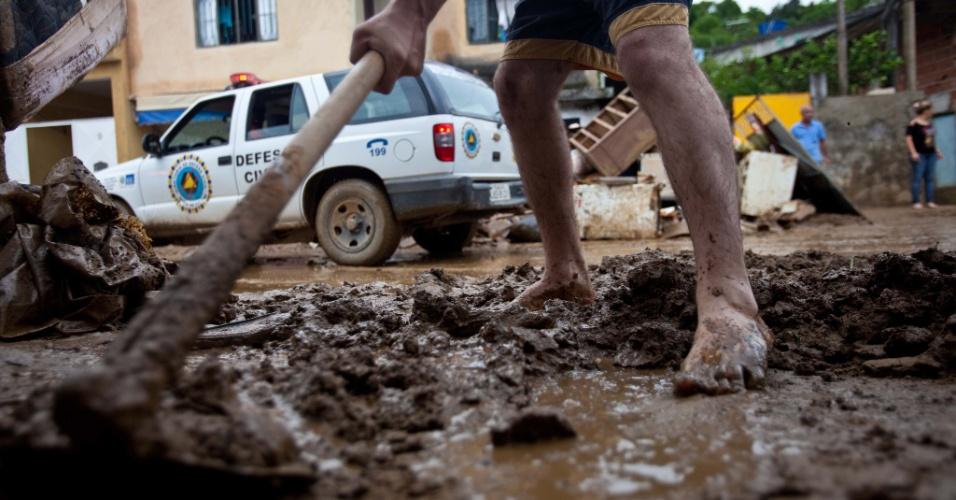 4.jan.2013 - Pessoas limpam suas casas após a tragédia em Xerém, Duque de Caxias (RJ). Pelo menos 300 pessoas foram desalojadas e uma pessoa morreu durante as enchentes