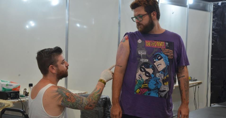 4.jan.2013 - Um tatuador trabalha durante feira internacional no Rio de Janeiro, que reúne cerca de mil tatuadores, artistas plásticos e body piercings, entre esta sexta-feira (4) e o domingo (6)