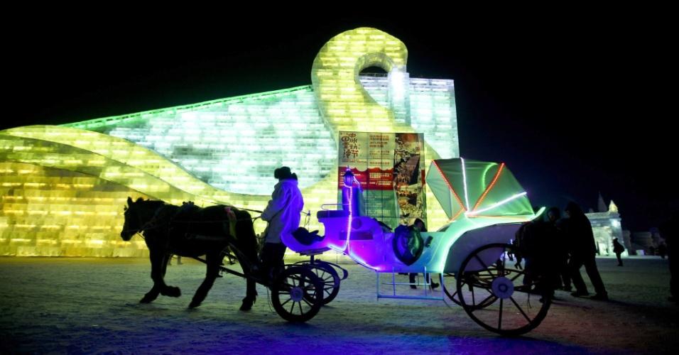 5.jan.2013 - Homem anda em charrete em frente a diversas esculturas de gelo durante o 29º Festival Internacional de gelo e neve de Harbin, na China