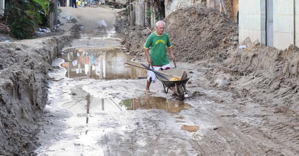 5.jan.2013 - Homem carrega carrinho de mão e enxada em meio ao rescaldo da destruição causada pelas chuvas no distrito de Xerém, em Duque de Caxias, na Baixada Fluminense. Com a trégua dos temporais na região, os moradores iniciaram as limpezas das casas e das ruas