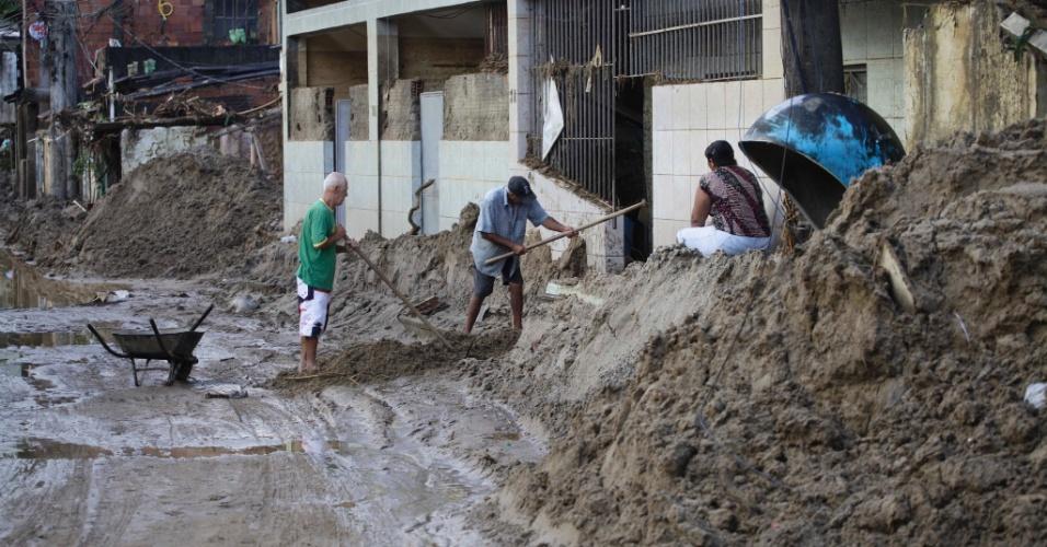 5.jan.2013 - Moradores iniciam a retirada da lama causada pelas chuvas no distrito de Xerém, em Duque de Caxias, na Baixada Fluminense