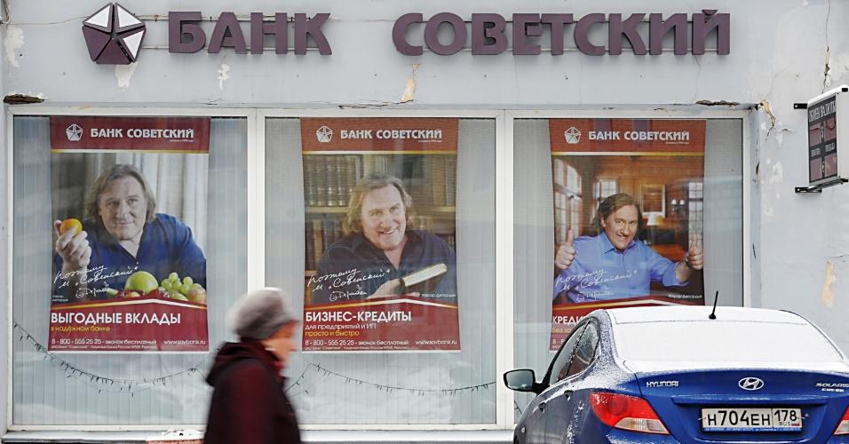 5.jan.2013 - Mulher passa em frente ao pequeno banco Sovetsky (Soviético), que usa Depardieu como