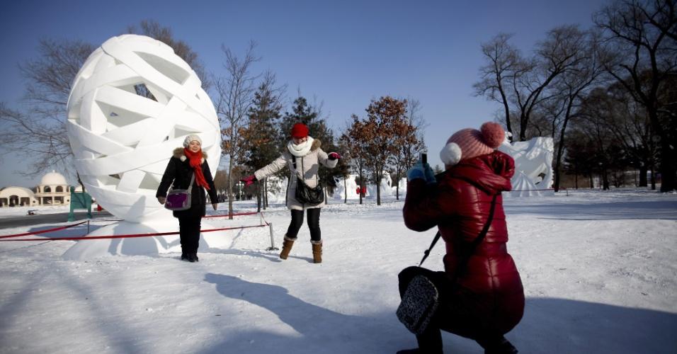 5.jan.2013 - Mulheres posam para foto em frente a uma escultura no Sun Island Park durante o 29º Festival Internacional de gelo e neve de Harbin, na China. A cidade fica na região norte do país na província de Heilongjiang