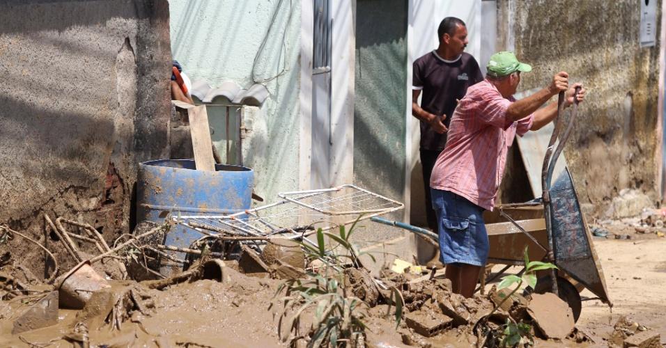 6.jan.2013 - Moradores retiram lama de casa e limpam os estragos da enchente que atingiu Xerém, distrito de Duque de Caxias, na Baixada Fluminense