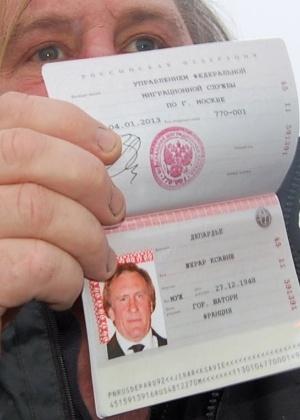 O francês Gerard Depardieu mostra seu novo passaporte com a nacionalidade russa no aeroporto de Mordóvia, a 640 km de Moscou - Caroline Larson/AFP