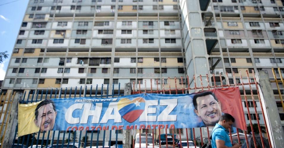 """7.jan.2013 - Homem caminha próximo a cartaz em apoio ao presidente Hugo Chávez em uma rua da favela """"23 de enero"""", em Caracas, na Venezuela, nesta segunda-feira (7). A incerteza sobre a presença do presidente Hugo Chávez - internado em Cuba após sua quarta cirurgia para combater um câncer - na cerimônia de posse para o seu novo mandato, dia 10 de janeiro, tem gerado a possibilidade de que a Venezuela tenha que definir na Justiça sobre quem tem o direito de chefiar o governo"""