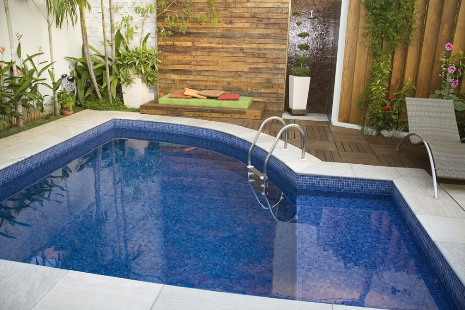 A piscina com formato irregular, projetada por Alessandra Morini, utiliza pastilhas cerâmicas para o revestimento interno e placas atérmicas na borda