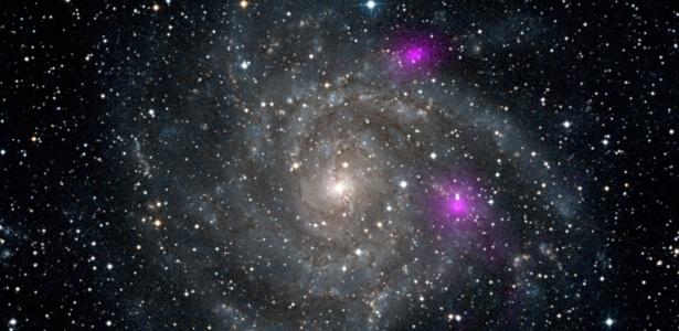 O observatório de raios X NuStar detectou dois buracos negros (pontos roxos) na galáxia espiral IC 342, que fica na constelação da Girafa (Camelopardalis), a 7 milhões de anos-luz da Terra - Nasa/JPL-Caltech/DSS