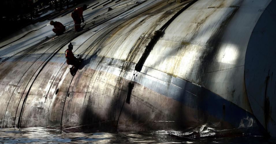 8.jan.2013 - Operários trabalham na estrutura do transatlântico Costa Concordia, que naufragou próximo à ilha de Giglio, na Itália