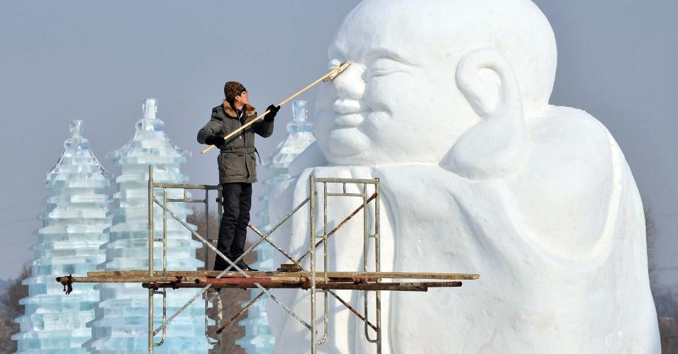 8.jan.2013- Homem limpa uma escultura de neve a dois dias do início Festival Internacional de Neve e Gelo, na província chinesa de Liaoning, que começa no dia 10 de janeiro