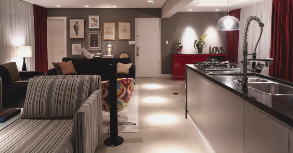 No projeto assinado pelos arquitetos Adine Woda e Artur Ferreira a cozinha com copa (18 m²) faz parte da área social (47 m²). O tom cinza nas paredes e o piso em porcelanato dão unidade aos ambientes segmentados pelo balcão de vidro e granito e pela viga que demarca a antiga parede