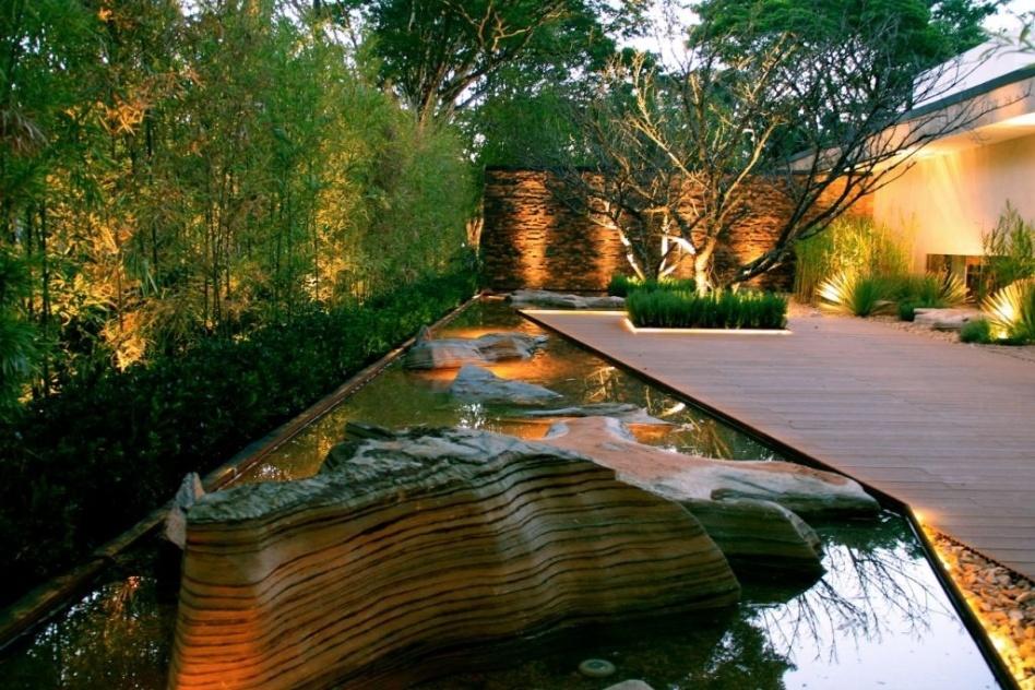Alex Hanazaki usou rochas rústicas de aspecto exótico para compor o visual do espelho d'água que contorna do a extensão do deck na área externa de uma residência