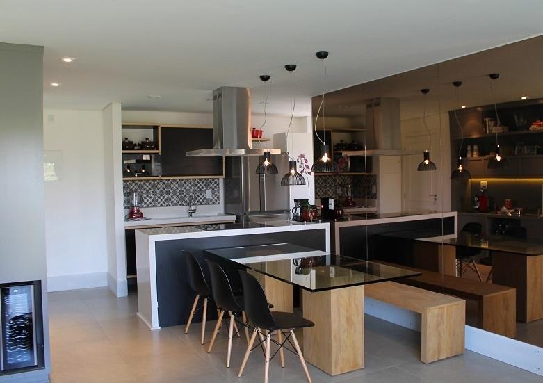 Com a reforma idealizada pela arquiteta Camila Gazola, o apartamento de 80 m² ganhou uma cozinha (4,5 m²) integrada à área de jantar (11,5 m²), graças a demolição da parede divisória. Agora quem cozinha fica de frente para quem está à mesa, com a instalação de um cooktop (GE) sobre a bancada de Marmoglass. O projeto integrou os ambientes graças ao desenho baseado em linhas retas, ao uso da madeira e às cores preto, branco e cinza