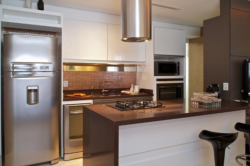 Na parede de fundo da cozinha, na reforma idealizada pela arquiteta Cinthia Garcia e pela designer Andréia Karalkovas, foram alocados os armários que embutem geladeira, forno e microndas, além da cuba com bancada de trabalho que também acopla a lava-louças