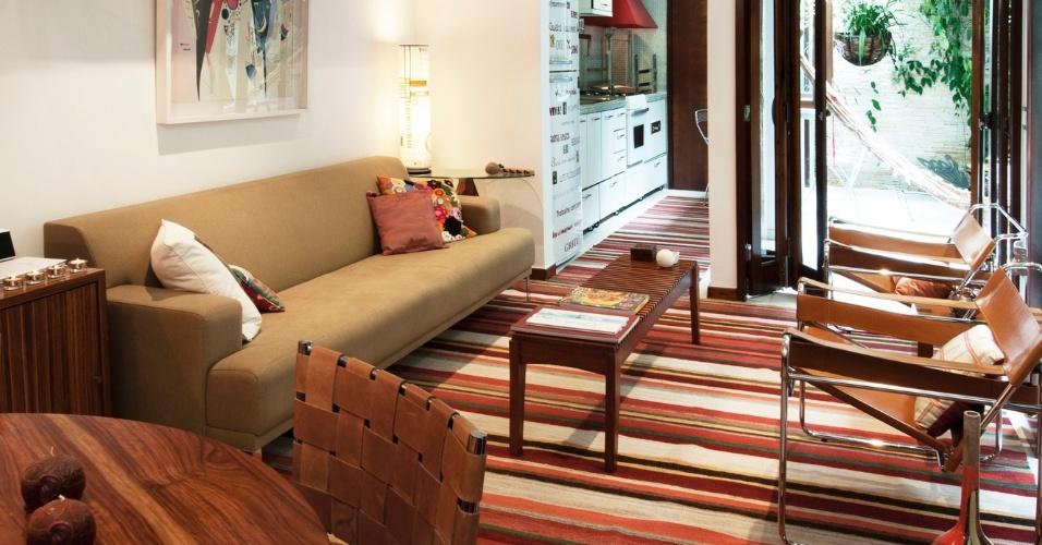 No projeto da arquiteta Crisa Santos, a cozinha (7,5 m²) funciona como ponto de interseção entre a sala (17 m²) e a varanda. Os eletrodomésticos e armários estão dispostos em uma das paredes, liberando a oposta para o balcão de refeições. Perceba que para integrar a cozinha com o estar, além optar por um vão sem porta, a arquiteta usou o tapete (Gaia) dando unidade aos ambientes