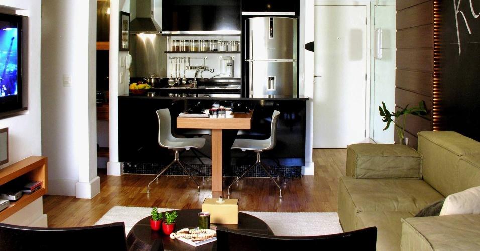 A cozinha americana (16 m²) foi a solução encontrada pela arquiteta Deborah Roig para otimizar o espaço do apartamento com 60 m². Para ganhar em área e integração, o projeto incluiu o balcão de vidro entre a sala e a cozinha, conectado-o à pequena mesa de refeições; além disso, a geladeira, a bancada com cuba e o fogão  foram distribuídos em