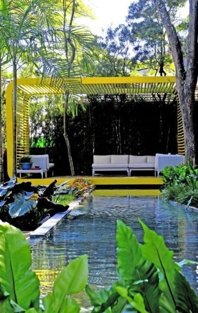 Diante do espelho d'água revestido de pedras há um ambiente de estar envolto em um estrutura em forma de fita de veneziana, pintada de um amarelo vivo que se destaca do verde do jardim. A proposta leva assinatura de  Alex Hanazaki