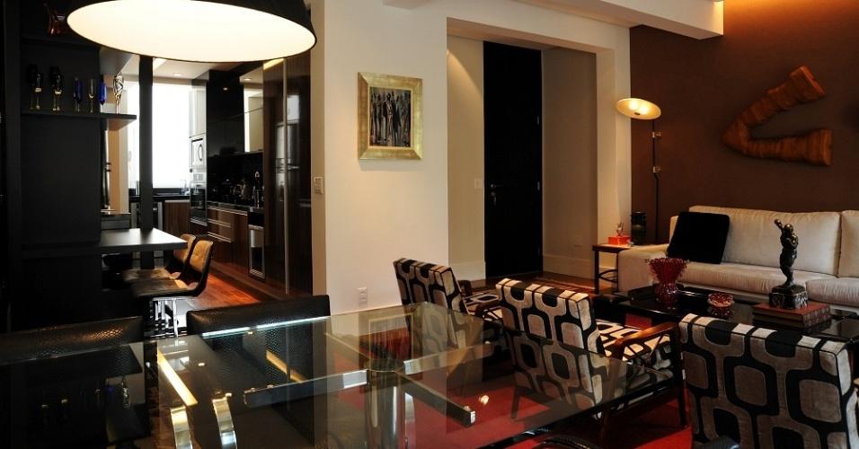 Entre a sala de jantar e a cozinha que foi equipada com armários da Elgin Cuisine, o designer Marcelo Mujalli idealizou uma bancada para cafés da manhã (ao fundo)